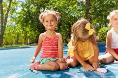 Милая притяжка маленьких девочек с мелом Стоковая Фотография