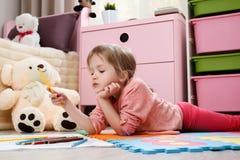 Милая притяжка маленькой девочки с покрашенными карандашами в roo ` s детей Стоковое фото RF