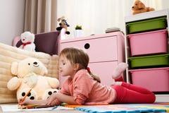 Милая притяжка маленькой девочки с покрашенными карандашами в roo ` s детей Стоковые Изображения