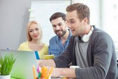 Милая дружелюбная команда используя тетрадь в офисе Стоковая Фотография RF