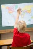 Милая рука повышения зрачка в классе на его столе Стоковая Фотография RF