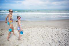 Милая семья бежать и играя на красивом пляже Стоковая Фотография
