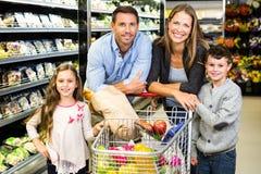 Милая семья делая посещение магазина бакалеи совместно стоковые фотографии rf