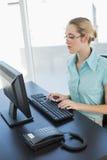 Милая сконцентрированная коммерсантка сидя на ее столе работая на ее компьютере Стоковые Изображения RF