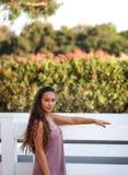 Милая склонность девушки против белой загородки стоковое фото