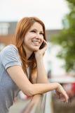 Милая склонность женщины на мосте звоня телефонный звонок Стоковые Изображения