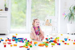 Милая смеясь над девушка малыша с красочными блоками Стоковая Фотография RF