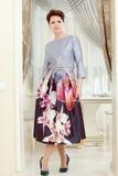 Милая средн-постаретая женщина представляя в элегантном платье Стоковые Фотографии RF
