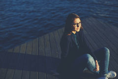 Милая счастливая девушка сидя на пристани и ждать ваш парня Стоковое Изображение RF