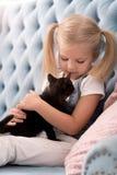 Милая сладостная девушка держа черного котенка Стоковое Изображение