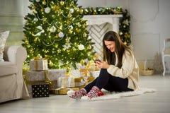 Милая темн-с волосами девушка сидит около рождественской елки с мобильным телефоном в руках Стоковое Изображение RF