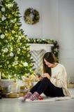 Милая темн-с волосами девушка сидит около рождественской елки с мобильным телефоном в руках Стоковое Фото