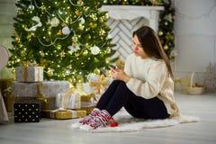 Милая темн-с волосами девушка сидит около рождественской елки с мобильным телефоном в руках Стоковая Фотография RF