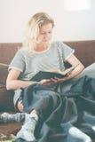 Милая тонизированная нежность кровати книги чтения девушки лежа Стоковые Изображения