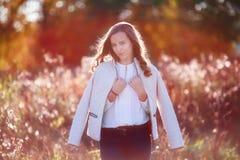 Милая усмехаясь девушка в солнечном свете упаденный спуск стенда осени цветастый выходит валы парка Стоковое фото RF