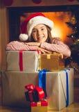 Милая усмехаясь девушка представляя с подарками на рождество на камине Стоковое Фото