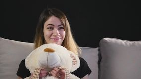Милая усмехаясь женщина сидя на кресле обнимая плюшевый медвежонка сток-видео