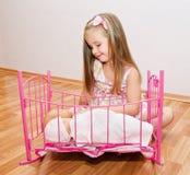 Милая усмехаясь маленькая девочка играя с ее newborn куклами младенца Стоковые Изображения