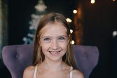 Милая усмехаясь маленькая девочка на предпосылке украшений рождества Стоковые Фото