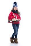 Милая усмехаясь маленькая девочка при курчавый стиль причёсок нося связанные свитер, шарф и шляпу при коньки изолированные на бел Стоковое Фото
