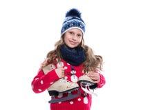 Милая усмехаясь маленькая девочка при курчавый стиль причёсок нося связанные свитер, шарф и шляпу при коньки изолированные на бел Стоковая Фотография