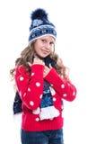 Милая усмехаясь маленькая девочка при курчавый стиль причёсок нося связанные свитер, шарф и шляпу при коньки изолированные на бел Стоковое Изображение