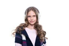 Милая усмехаясь маленькая девочка при курчавый стиль причёсок нося красочный свитер и головной убор изолированный на белой предпо Стоковые Фото