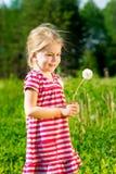 Милая усмехаясь маленькая девочка с одуванчиком в ее руках делает желание Стоковое Изображение RF