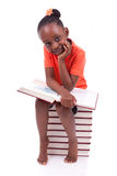 Милая черная Афро-американская маленькая девочка читая книгу - африканца стоковые изображения