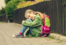 Милая школьница сидя на улице Стоковая Фотография