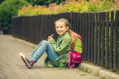 Милая школьница сидя на улице Стоковое Фото