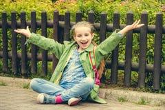 Милая школьница сидя на улице Стоковые Изображения
