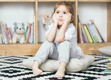 Милая эмоциональная маленькая девочка унылая о книгах чтения Стоковое Изображение