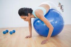 Милая sporty тренировка женщины на шарике фитнеса Стоковые Фото