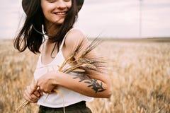 Милое брюнет выбирает цветки в поле пшеницы Стоковые Изображения