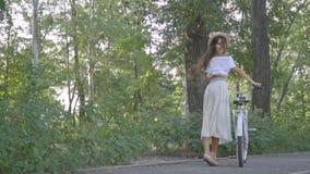 Милое брюнет в белой юбке, блузке в парке держа велосипед города, смеясь над и смотря назад и смеясь над весело акции видеоматериалы