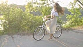 Милое брюнет в длинной юбке, белой блузке и развевать соломенная шляпа едет на дороге рекой на белом велосипеде города видеоматериал