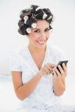 Милое брюнет в роликах волос используя smartphone на кровати смотря камеру Стоковые Фотографии RF