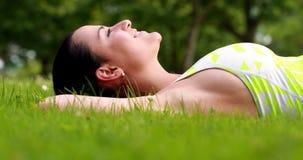 Милое брюнет лежа вниз на траве видеоматериал
