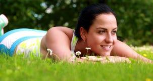 Милое брюнет лежа вниз на траве сток-видео
