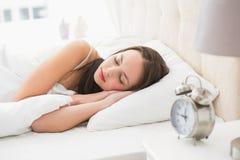 Милое брюнет лежа в спать кровати Стоковое Фото