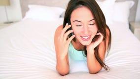 Милое брюнет лежа на кровати говоря на телефоне акции видеоматериалы