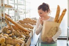 Милое брюнет держа сумку хлеба Стоковая Фотография