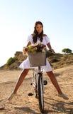 Милое брюнет ехать велосипед вдоль морского побережья Стоковое фото RF
