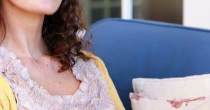 Милое брюнет ослабляя на кресле с компьтер-книжкой сток-видео