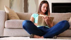 Милое брюнет ослабляя на чтении половика сток-видео