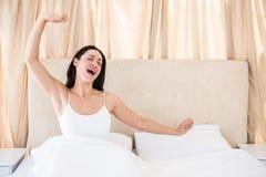 Милое брюнет просыпая вверх на кровати Стоковое Изображение RF