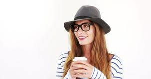 Милое брюнет с eyeglasses и кофе шляпы выпивая видеоматериал