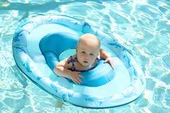 Милое заплывание ребёнка в бассейне в шлюпке Стоковое Фото