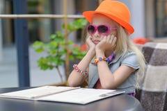 Милое меню чтения ребенка в кафе Стоковые Изображения